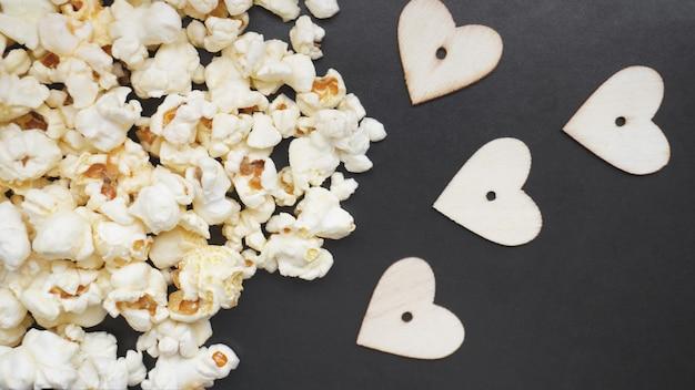 Hou van popcorn concept. horizontale foto. zoet eten. klassieke gezouten popcorn met houten hartjes op een zwarte ondergrond