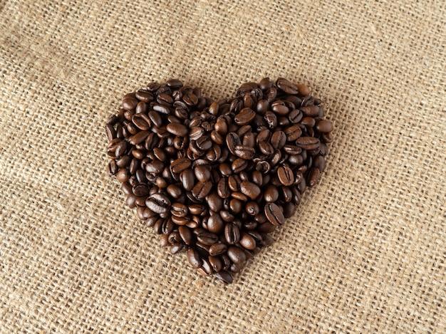 Hou van vorm koffiebonen op de achtergrond van de linnentextuur