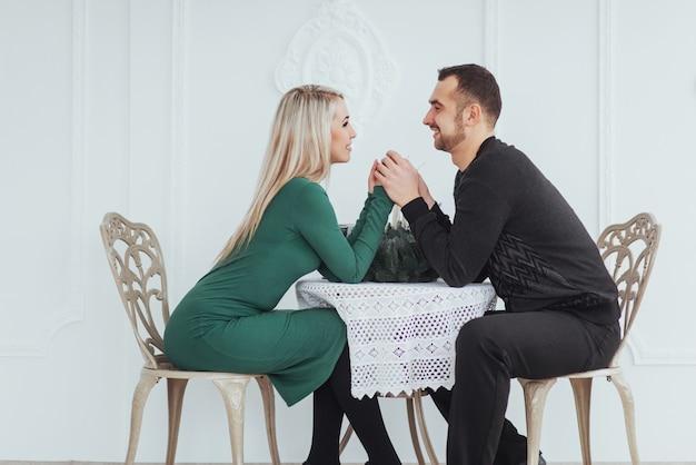 Hou van zitten aan de tafel paar man en vrouw met wijnglazen op wit in het restaurant. valentijnsdiner