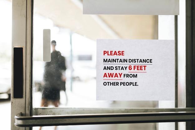 Houd afstand en blijf op anderhalve meter afstand van een papieren bordje op een glazen deur van andere mensen