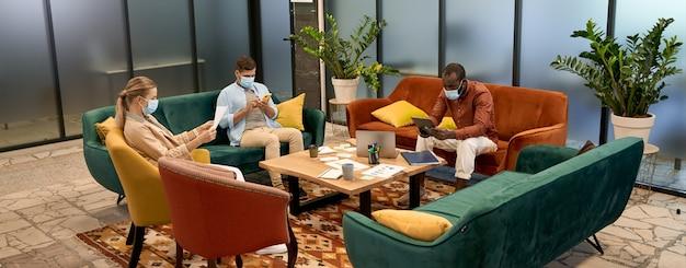 Houd afstand jonge kantoormedewerkers die medische beschermende maskers dragen die werken of ontspannen