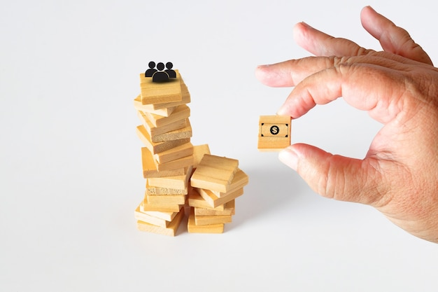 Houd een houten kubusspeelgoed met bankbiljetpictogram in de hand om naar de toren te gaan.
