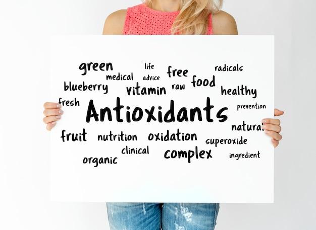 Houd een plakkaat vast met de woordkaart van antioxidanten
