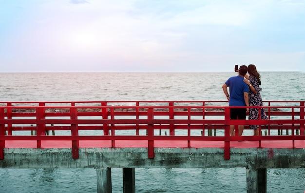 Houd een romantisch moment om een foto te maken met de mobiele telefoon op de rode brug op zee