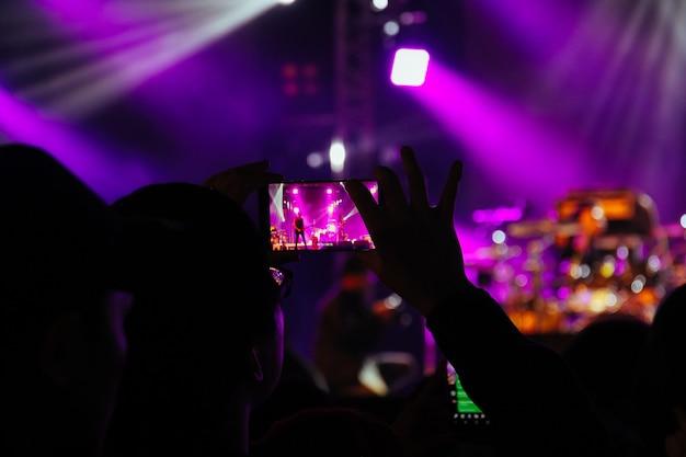 Houd een smartphone vast die foto's maakt of video's opneemt van een concertpodium