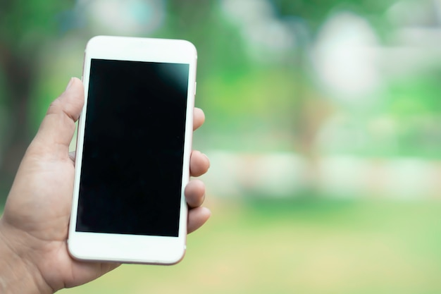 Houd en gebruik slimme mobiele telefoon om te communiceren op buiten in park.