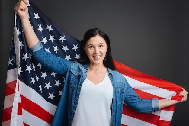 Houd het hoog en trots. schitterende inspirerende mooie dame die onafhankelijkheidsdag viert en de nationale vlag omhoog houdt terwijl status geïsoleerd op grijze achtergrond