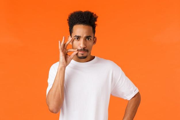 Houd je mond dicht. ernstige en gekke, bazige afro-amerikaanse man eis zwijgen, zip mond en zuigen lippen fronsen, grimace lastiggevallen, verbieden spreken, staande oranje boos