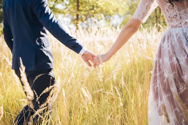Houd me vast en laat nooit meer los. gelukkig pasgetrouwden hand in hand