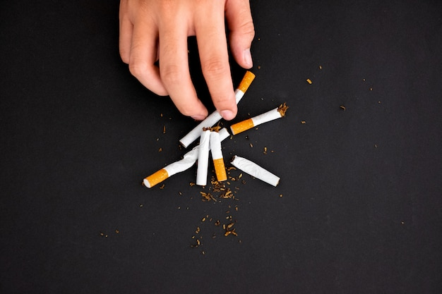 Houd met op rokend, de sigaret van de handgreep vernietigt geïsoleerd op zwarte