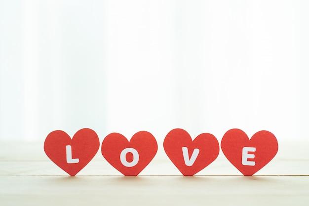 Houd van rood hart vier op houten vloer