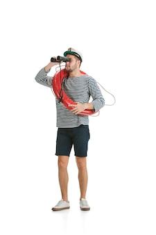 Houden reddingslijn en verrekijker. kaukasische mannelijke matroos in uniform op witte achtergrond. jonge man met behulp van moderne apparaten en gadgets in zijn werk. concept van tech, professioneel beroep, baan van zeeman.