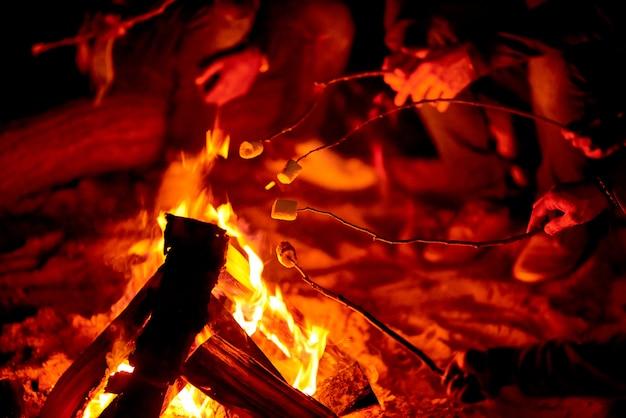 Houden stokjes met marshmallows boven kampvuur