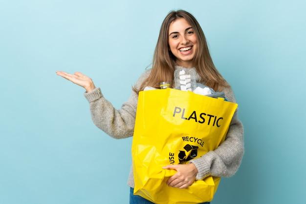 Houdend een zakhoogtepunt van plastic flessen over geïsoleerde blauwe holding copyspace denkbeeldig op de palm te recycleren