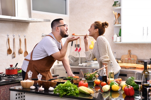 Houdend van jong aziatisch paar die in keuken koken die gezond voedsel maken samen voelend pret