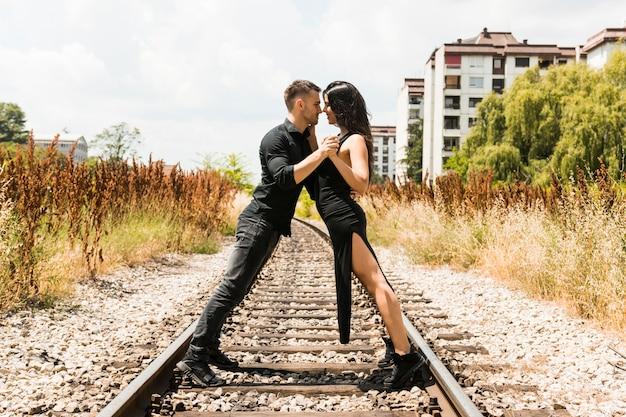 Houdend van jong paar die zich van aangezicht tot aangezicht op de spoorweg stellen