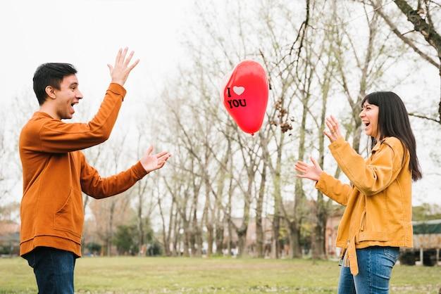 Houdend van paar die ballon in openlucht werpen
