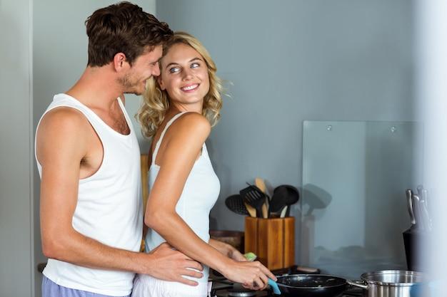 Houdende van man die vrouw omhelst terwijl het koken van voedsel in keuken