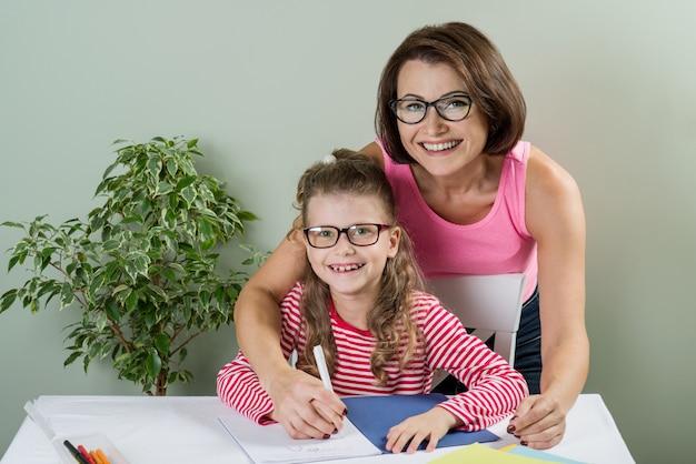 Houdende van moeder die haar dochter helpt in haar notitieboekje schrijven