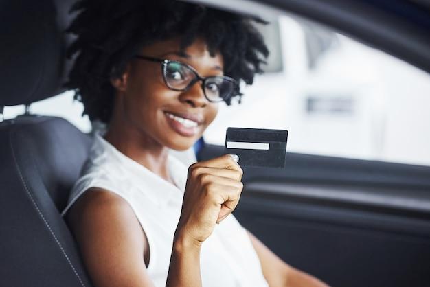 Houdt creditcard. jonge afro-amerikaanse vrouw zit binnenkant van nieuwe moderne auto.