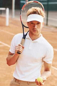 Houdt de bal in de hand. jonge tennisser in sportieve kleding is buiten op het veld.
