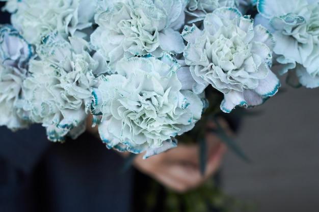 Houdt de close-up vrouwelijke handen een boeket van blauwe anjers op grijze muur