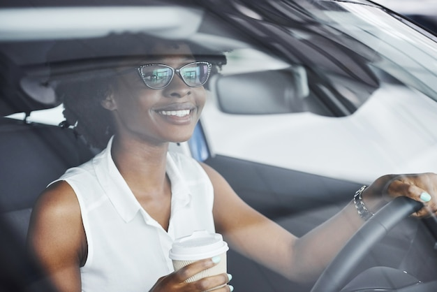 Houdt een kopje drank vast. jonge afro-amerikaanse vrouw zit binnenkant van nieuwe moderne auto.