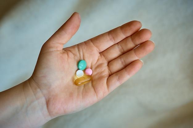 Houdt een pil in haar hand, hoofdpijn en kou