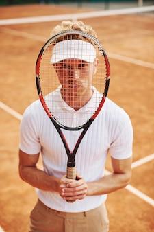 Houdt racket in handen. jonge tennisser in sportieve kleding is buiten op het veld.