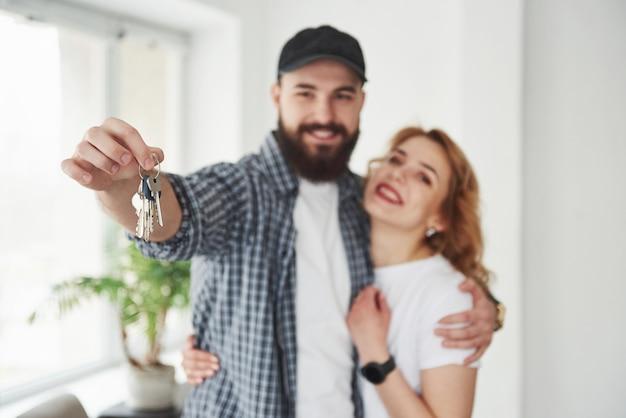 Houdt sleutels vast. gelukkig paar samen in hun nieuwe huis. conceptie van verhuizen