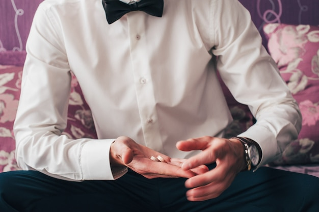 Houdt twee trouwringen in de hand