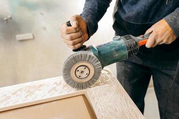 Hout borstelen met een elektrische roterende borstelslijper. houtbewerking.