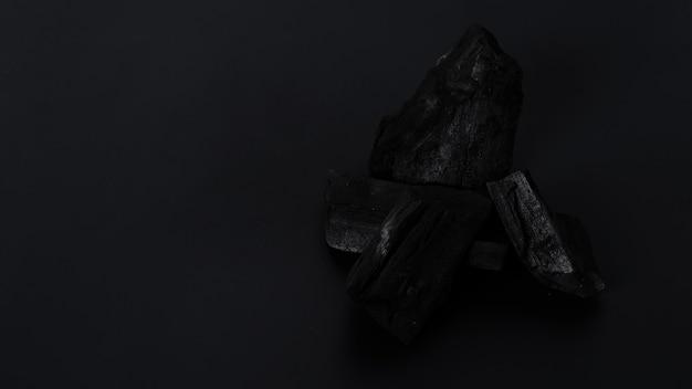 Hout houtskool. zwarte houtskool op zwarte getextureerde vloer. gebruikt voor het koken van grill of andere industrieën. natuurlijke houtskool. zwart koolstofresidu geproduceerd door sterk verhittend hout. voor traditionele bbq