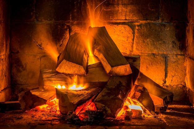 Hout stoken in een gezellige open haard thuis, warm houden.