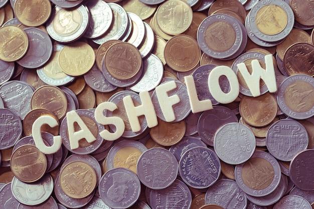 Hout tekst cashflow op munten achtergrond, business en finance concept