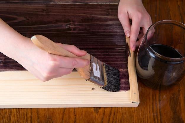 Hout verven met een penseel in de kleur van ebbenhout