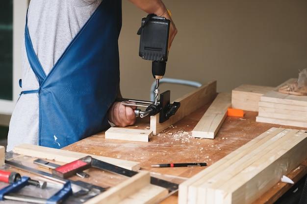 Houtbewerkende ondernemers gebruiken een boor door de houtgaten om houten tafels voor klanten te monteren en te bouwen.