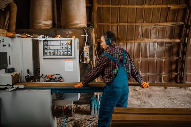 Houtbewerker werkt op machine, houtindustrie