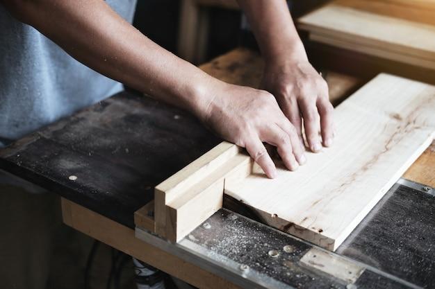 Houtbewerkers gebruiken zaagbladen om stukken hout te zagen om houten tafels voor te monteren en te bouwen