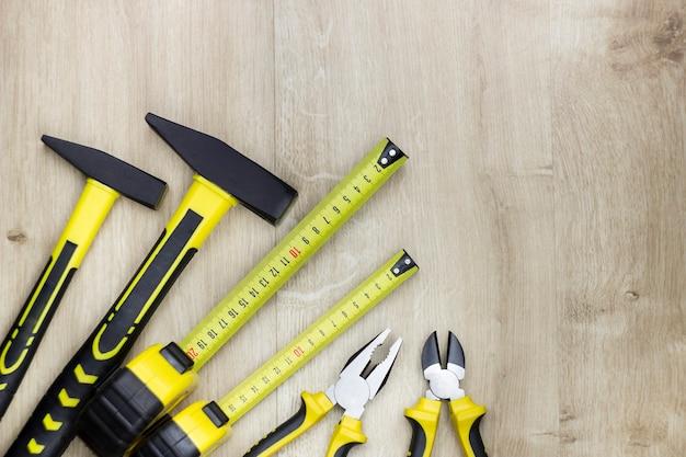 Houtbewerking en huishoudelijk gereedschap op hout achtergrond. bovenaanzicht op hamer, tang, draadknipper en stalen meetlint liniaal
