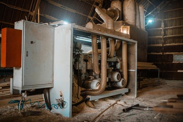 Houtbewerkingsmachine in zaagsel, niemand, houtindustrie, timmerwerk. houtverwerking op fabriek, boszagen in houtzagerij, zagerij