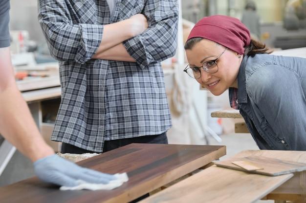 Houtbewerkingsworkshop, arbeider die houten plankclose-up vernissen