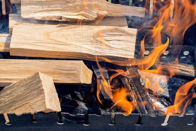 Houtblokken branden in de grill