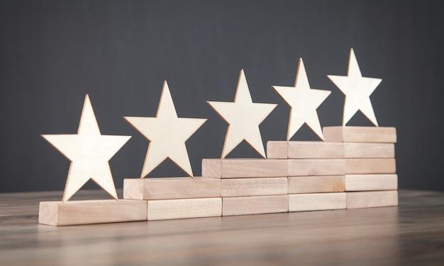 Houten 5 sterren op houten blok. beoordeling verhogen