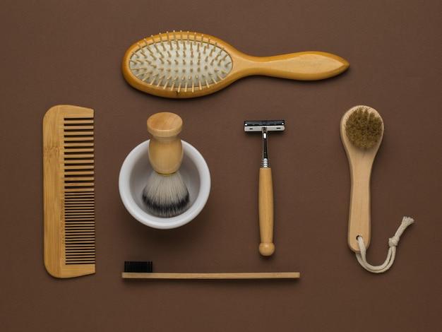 Houten accessoires voor scheren, haren en tanden poetsen op een bruine achtergrond. herenaccessoires voor uiterlijke verzorging. plat leggen.