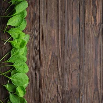 Houten achtergrond met de bladeren van de babyspinazie. kopieer ruimte. gezond eten concept
