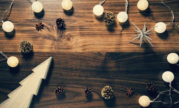 Houten achtergrond met decoratieve kerstboom, slinger en dennenappels.