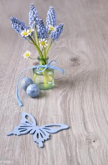 Houten achtergrond met lentebloemen en kwartel eieren