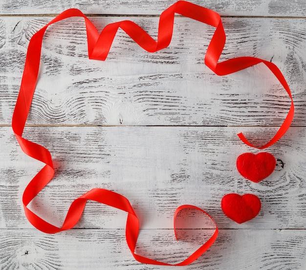 Houten achtergrond met rood lint en snoep harten
