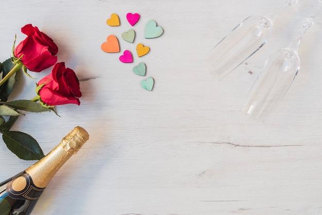 Houten achtergrond met rozen, harten, glazen champagne, champagne, kopieer ruimte